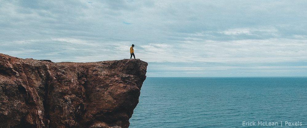 Un hombre en una roca frente al mar, riesgos